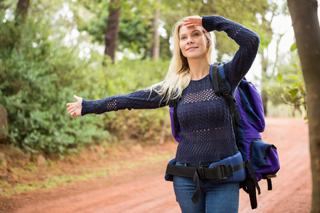 adventuring: Pretty hitchhiker sticking thumb out on a crossing path Stock Photo