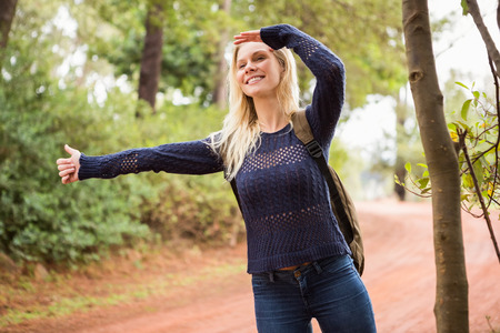 hitch hiker: Pretty hitchhiker sticking thumb out on a crossing path Stock Photo