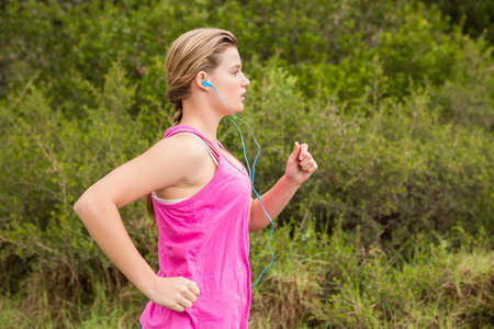 cross street with care: Pretty blonde athlete jogging and listening to music in the nature
