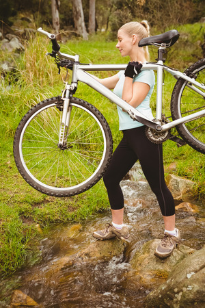 adventuring: Serious fit woman lifting her bike while crossing a river Stock Photo