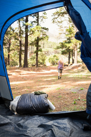 adventuring: Blonde camper walking away from tent in the nature Stock Photo