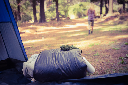 adventuring: Sleeping bag in front of blonde camper walking away in the nature Stock Photo