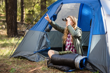adventuring: Blonde camper looking through binoculars while sitting in tent