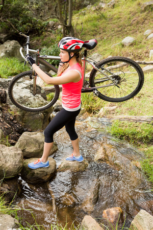 cross street with care: Blonde athlete carrying her mountain bike over stream in the nature