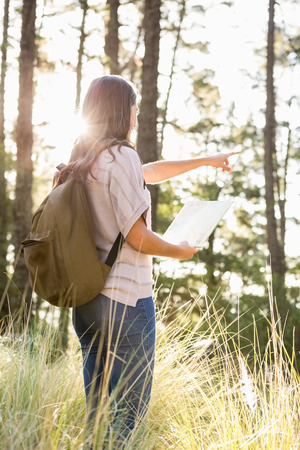 far away: Brunette hiker with map pointing far away in the nature Stock Photo