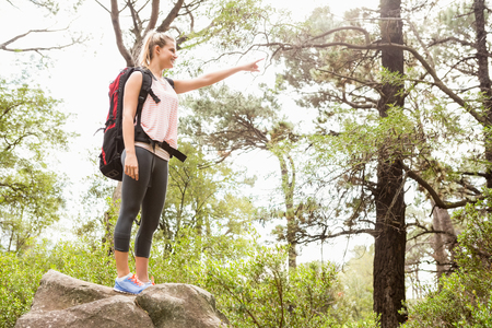 Smiling blonde hiker pointing far away in the nature