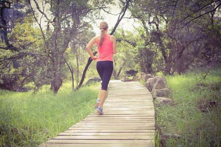 sport fitness: Blonde athlete jogging on wooden path in nature