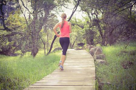 actividades recreativas: Trotar atleta rubia en el camino de madera en la naturaleza Foto de archivo