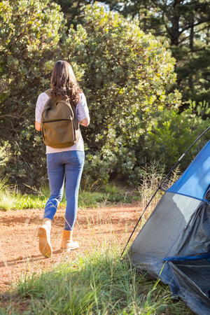 adventuring: Brunette camper walking away from tent in the nature