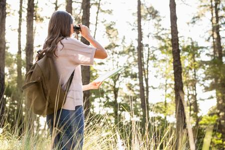 adventuring: Female hiker looking through the binoculars in the nature Stock Photo