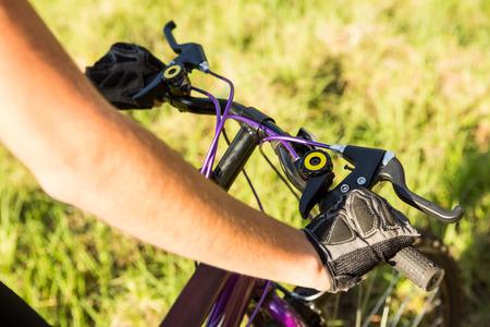 adventuring: Woman mountain biking and holding handlebars in the nature Stock Photo
