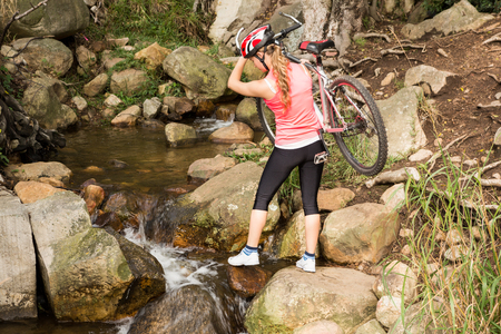 adventuring: Blonde athlete carrying her mountain bike over stream in the nature