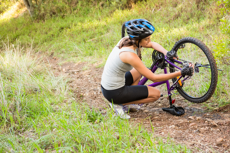 adventuring: Athletic brunette repairing her mountain bike in the nature