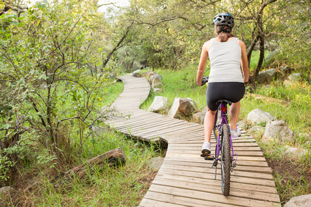 healthy path: Rear view of athletic brunette mountain biking on wooden path in the nature Stock Photo