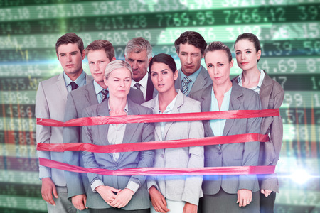 fastened: Upset business team fastened with adhesive tape  against stocks and shares Stock Photo