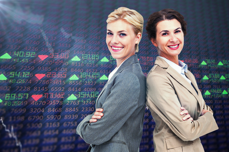 altogether: Serious businesswomen standing back on back against stocks and shares Stock Photo
