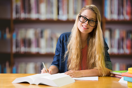 biblioteca: Estudiante que estudia en la biblioteca contra los libros en el escritorio en la biblioteca Foto de archivo