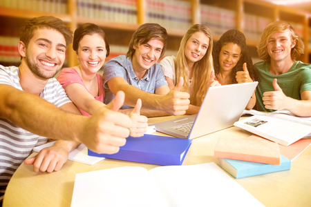 sit up: College students gesturing thumbs up in library against close up of a bookshelf