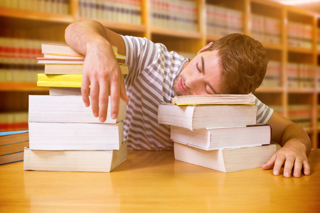 slump: Student asleep in the library against close up of a bookshelf