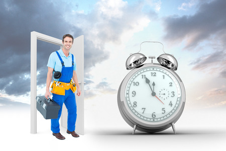 tool box: Happy plumber carrying tool box against alarm clock counting down to twelve Stock Photo