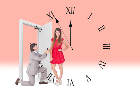against the clock: Hipster on bended knee doing a marriage proposal to his girlfriend  against clock counting down to midnight
