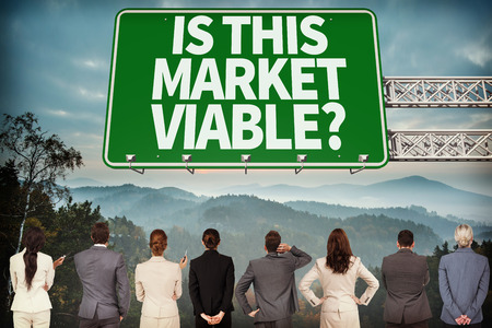 viable: Business team against green road sign by mountains Stock Photo