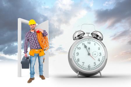 puerta abierta: caja de herramienta de sujeción personal de mantenimiento y el multímetro contra reloj despertador cuenta atrás para las doce