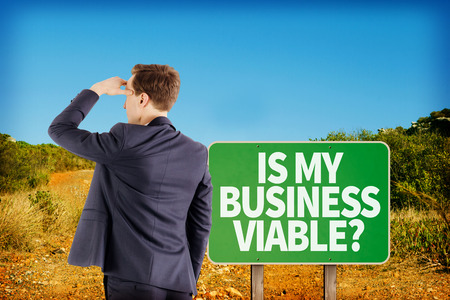 viable: Wear view of businessman looking away  against green road sign by mountain trail Stock Photo