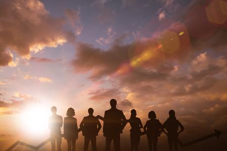 business team with arrow against sun shining