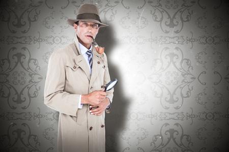 spy camera: Spy looking through magnifier against elegant patterned wallpaper in grey tones