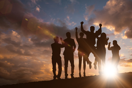 african american silhouette: Silhouetters celebrating against clouds Stock Photo