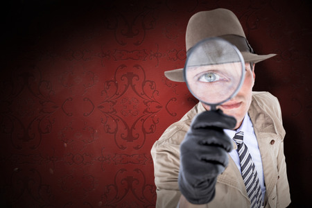 patterned wallpaper: Spy looking through magnifier against elegant patterned wallpaper in red tones