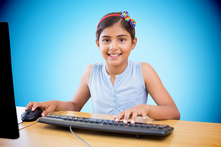 digital learning: School kid on computer against blue background with vignette Stock Photo