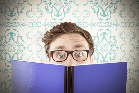 patterned wallpaper: Geeky student reading a book against elegant patterned wallpaper in blue and cream Stock Photo