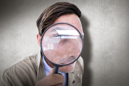fourties: Spy looking through magnifier against white and grey background