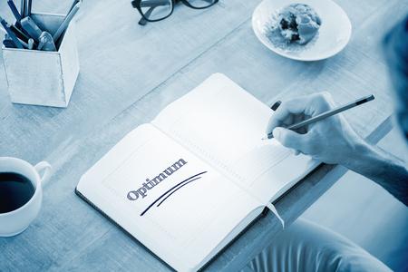 optimum: The word optimum against man writing notes on diary