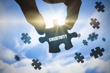 buzzword: The word creativity  and hand holding jigsaw piece against blue sky