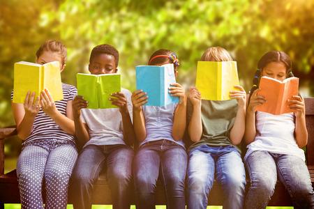 дети: Дети читают книги в парке против деревьев и луговых в парке