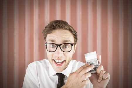geeky: Geeky businessman using a calculator against background Stock Photo