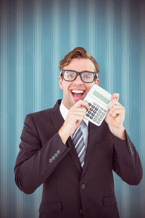 cheesy grin: Geeky businessman pointing to calculator  against blue background