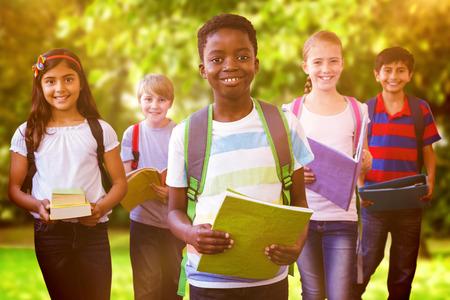 ni�os en la escuela: Ni�os sonrientes de la escuela en el pasillo de la escuela contra los �rboles y prado en el parque