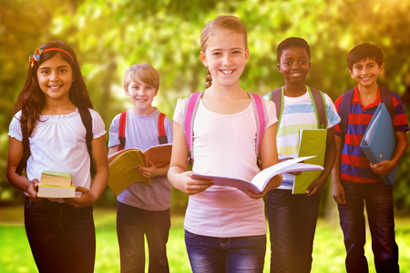 Smiling little school kids in school corridor against trees and meadow in the park Stock Photo