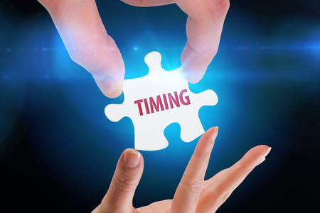 The word timing and hands holding jigsaw against blue background with vignette