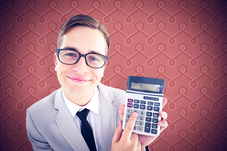 geeky: Geeky smiling businessman showing calculator against background Stock Photo