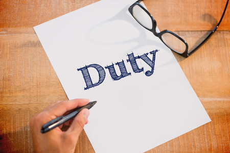 dutiful: The word duty against left hand writing on white page on working desk