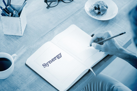 synergy: The word synergy against man writing notes on diary