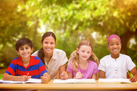 Pretty teacher helping pupils in library against trees and meadow in the park Stock Photo