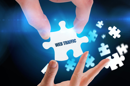 web traffic: The word web traffic and hands holding jigsaw against blue background with vignette