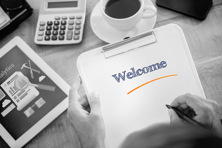 welcome desk: The word welcome and man writing on clipboard on working desk against business analytics Stock Photo