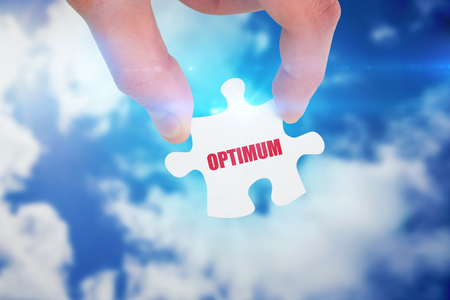 optimum: The word optimum and hand holding jigsaw piece against bright blue sky with clouds